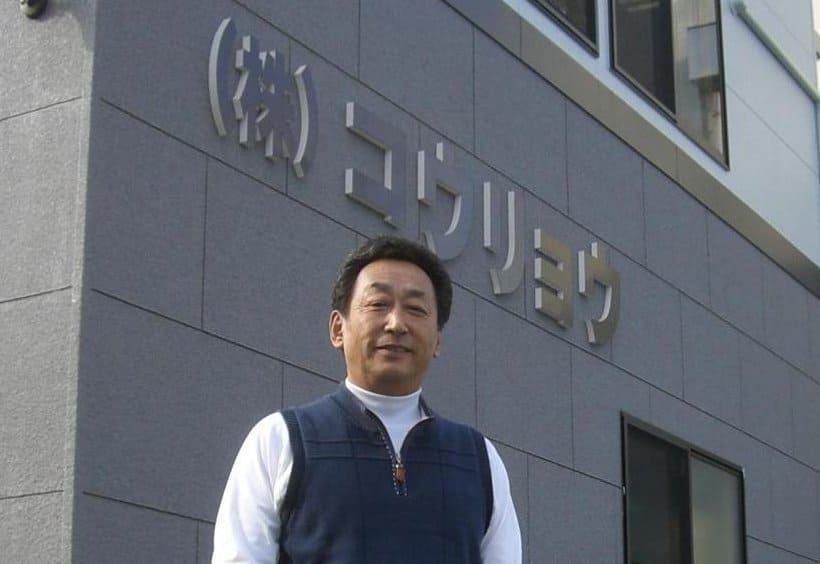 金田純一、社屋を背景に記念写真